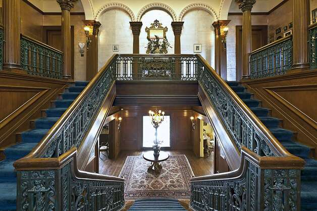 This grand double staircase is carved from dark wood and has wrought-iron balusters. A Tiffany-style stained glass skylight illuminates this double-story atrium. Photo: Cleber Dealancar