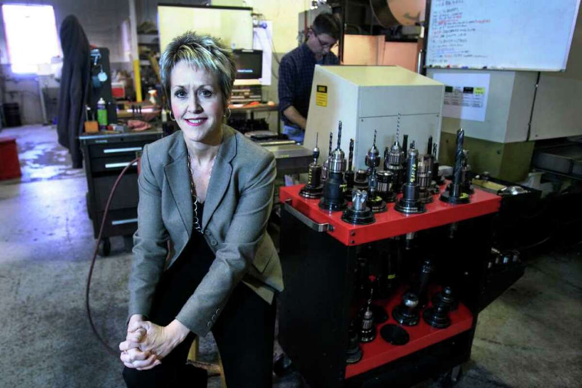 In this Feb. 8, 2012 photo, Laurie Schmald Moncrieff president of Schmald Tool and Die in Burton, Mich., poses in her shop. Moncrieff says she began shifting from autos to the green energy, aerospace and defense industries when demand collapsed. (AP Photo/Carlos Osorio)