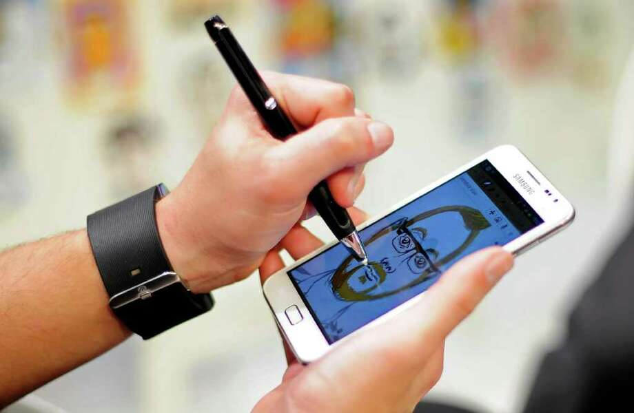 A visitor uses a stylus to draw a picture on a new Samsung Galaxy Note smartphone Monday at the Mobile World Congress in Barcelona, Spain. Photo: MANU FERNANDEZ / AP