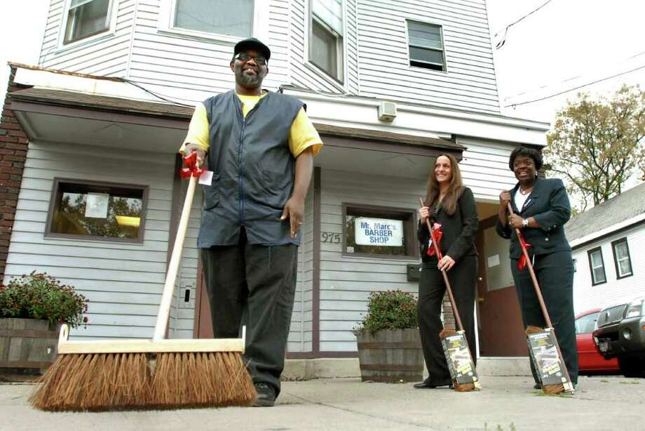 Times Union staff photo by Cindy Schultz -- Marc Thompson, owner of Mr. Marc's Barber Shop, left, tries out the broom provided him by Operation Clean Sweep members Keri Pratico, center, and Marion Porterfield, right, on Wednesday, Oct. 24, 2007, in Schenectady, N.Y. Pratico is administrative assistant of the Schenectady County Community Business Center and Porterfield is site coordinator for Weed and Seed. (WITH NELSON STORY) Photo: CINDY SCHULTZ / ALBANY TIMES UNION