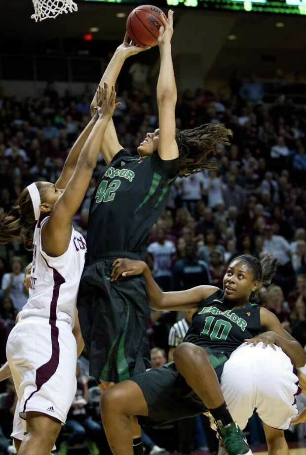 Baylor center Brittney Griner (42) shoots over Texas A&M center Karla Gilbert (34) as Destiny Williams (10) takes a tumble during the second half of a NCAA women's basketball game at Reed Arena on Monday, Feb. 27, 2012, in College Station. Photo: Smiley N. Pool, Houston Chronicle / © 2012  Houston Chronicle