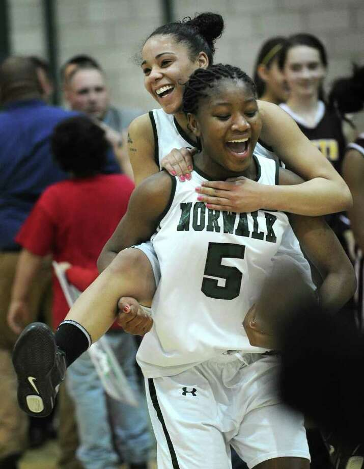 Norwalk's Erica Cohens leaps on the shoulders of teammate Denisha Gardener following their victory over South Windsor in the opening round of the Class LL state basketball tournament at Norwalk High School on Monday, February 27, 2012. Photo: Brian A. Pounds / Connecticut Post