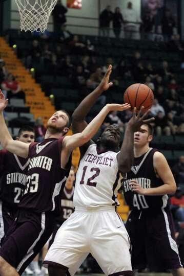 Watervliet's Antoine Johnson, center, battles Stillwater's Shawn McNeil, left, for the ball during t