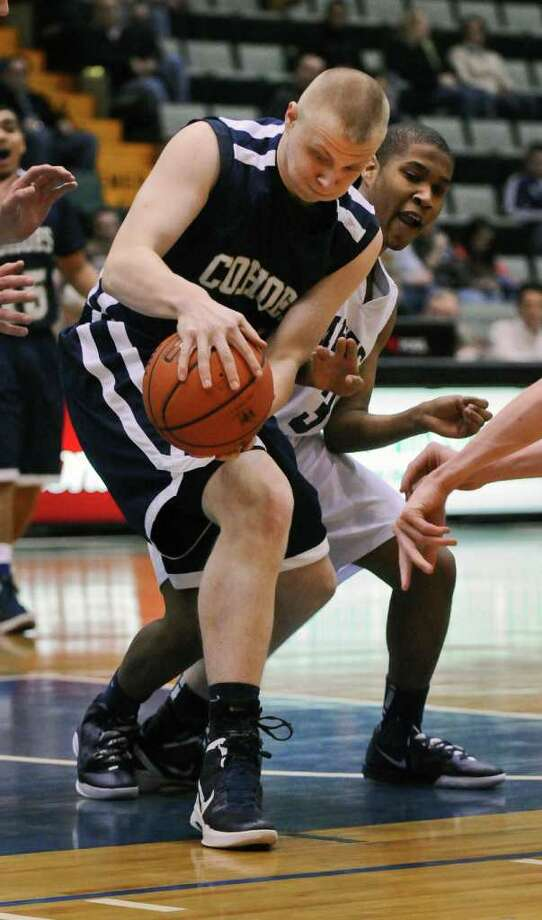 Cohoes player Kevin Napier, left, battles Mekeel Christian Academy's Courtney Penson, right, for the ball during the first half of their 71-57 win over Mekeel in a Section II Class B semifinal at the Glens Falls Civic Center on Monday night Feb. 27, 2012 in Glens Falls, N.Y. (Philip Kamrass / Times Union ) Photo: Philip Kamrass / 00016567A