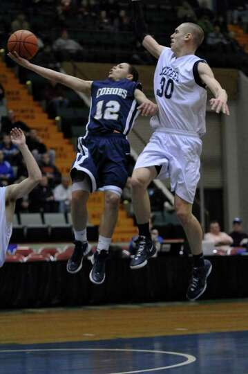 Cohoes player Elijah Newsome drives to the basket while  Mekeel Christian Academy's Collin Stewart,