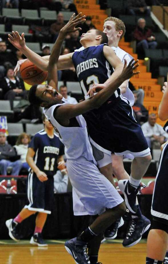 Cohoes player Elijah Newsome drives to the basket while  Mekeel Christian Academy's Ohenio Miller, left, and Caleb Stewart, right, defend him during the second half of Cohoes  71-57 victory in a Section II Class B semifinal at the Glens Falls Civic Center on Monday night Feb. 27, 2012 in Glens Falls, N.Y. (Philip Kamrass / Times Union ) Photo: Philip Kamrass / 00016567A