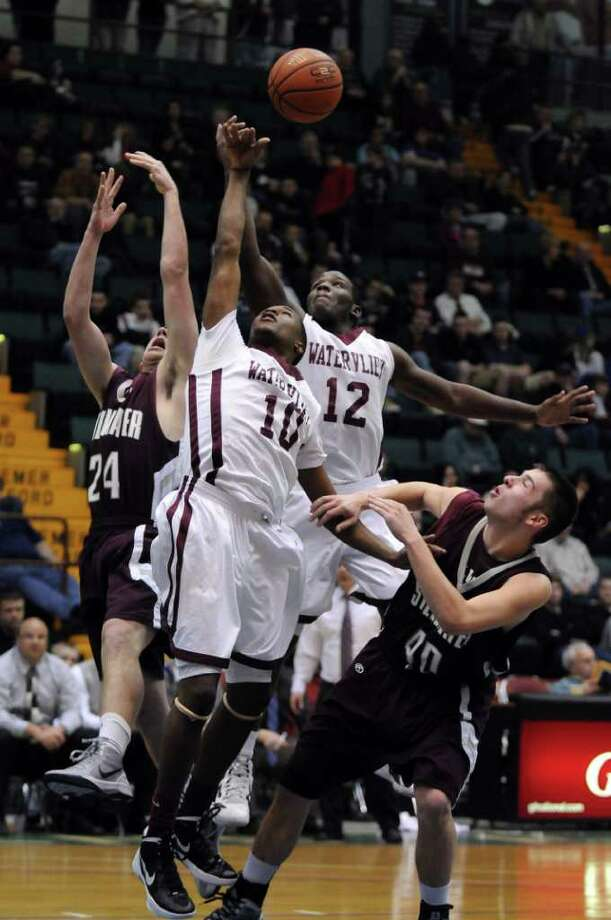 Watervliet's Antoine Johnson, 12, right, and Tyler McLeod, 10, left,  battles Stillwater's Rick McBride, 24, far left, and Ryan DeCota, 40, far right,  for the ball during the second half of Watervliet's 75-40 victory in a Section II Class B semifinal at the Glens Falls Civic Center on Monday night Feb. 27, 2012 in Glens Falls, N.Y. (Philip Kamrass / Times Union ) Photo: Philip Kamrass / 00016567A