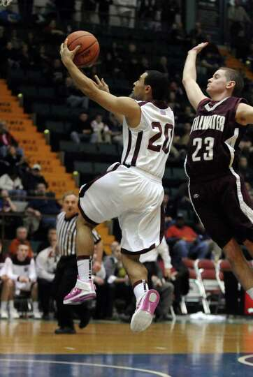 Watervliet's Jon Parker is about to be fouled by Stillwater's Evan Pafundi, right, as he puts up a s