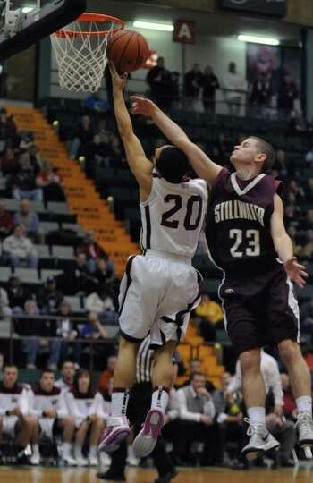 Watervliet's Jon Parker is fouled by Stillwater's Evan Pafundi, right, as he puts up a shot during t