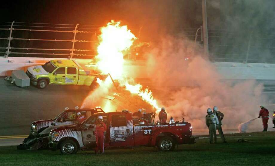 Emergency workers try to put out a fire after Juan Pablo Montoya's car struck the truck during the NASCAR Daytona 500 auto race at Daytona International Speedway in Daytona Beach, Fla., Monday, Feb. 27, 2012. (AP Photo/Bill Friel) Photo: Bill Friel