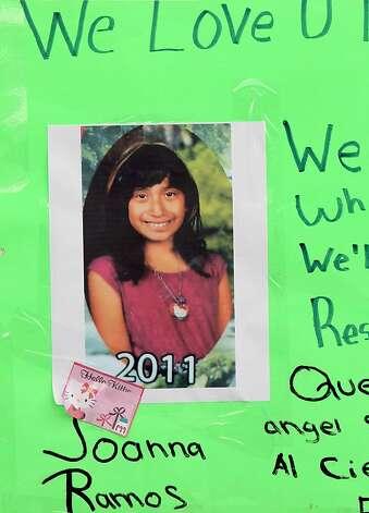 A photo of Joanna Ramos, 10,with a note,  is left at a memorial outside Willard Elementary school  in Long Beach, Calif. on Monday Feb. 27, 2012.  Ramos, who died after a fight with an 11-year-old in an alley near their elementary school underwent emergency surgery for a blood clot on her brain before her death, her sister said Monday. (AP Photo/Nick Ut) Photo: Nick Ut, Associated Press