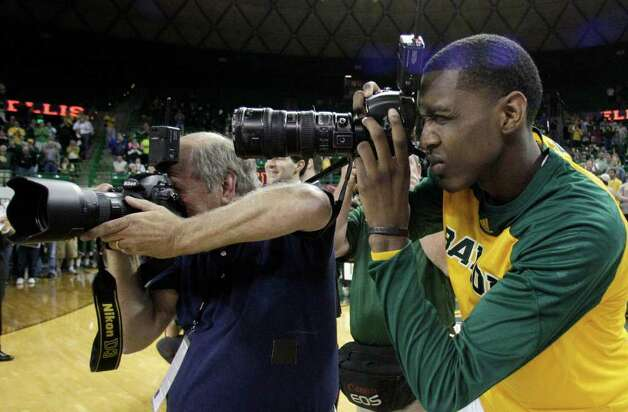 Baylor 's Quincy Miller, right, borrows a camera from Waco Tribune Herald photographer Rod Aydelotte, left, to make some photographs of the post game celebration following an NCAA college basketball game against Texas Tech Monday, Feb. 27, 2012, in Waco. Baylor celebrated senior night for a few of the players in the 77-48 win over Texas Tech. Photo: Associated Press