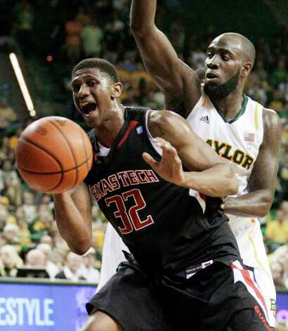 Texas Tech 's Jordan Tolbert (32) loses control of the ball under pressure from Baylor 's Quincy Acy, right, in the first half of an NCAA college basketball game Monday, Feb. 27, 2012, in Waco. Photo: Associated Press