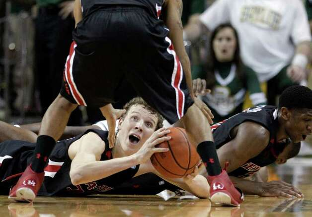 Texas Tech 's Clark Lammert, bottom, prepares to pass the ball to Javarez Willis, top, after scrambling on the floor for a loose ball in the second half of an NCAA college basketball game against Baylor  Monday, Feb. 27, 2012, in Waco. Baylor won 77-48. Photo: Associated Press