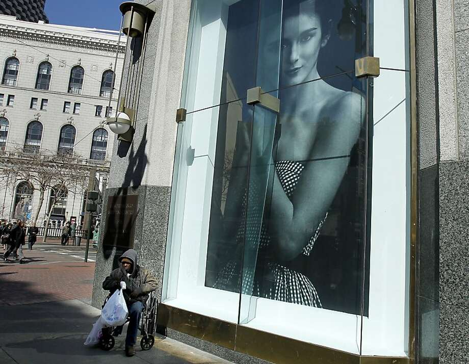 A portrait of prosperity at the Westfield San Francisco Centre stands in contrast to a woman on the street below. Photo: Brant Ward, The Chronicle