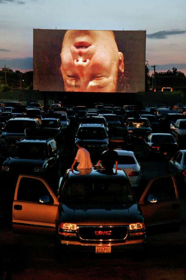 John Cusak makes a star turn during '1408' playing at the Mission Drive-In on Aug. 24, 2007. The drive-in re-opened after being vandalized earlier this year. The movie theater opened in March 1948 and is a South Side landmark.  Photo: NICOLE FRUGE, SAN ANTONIO EXPRESS-NEWS / SAN ANTONIO EXPRESS-NEWS