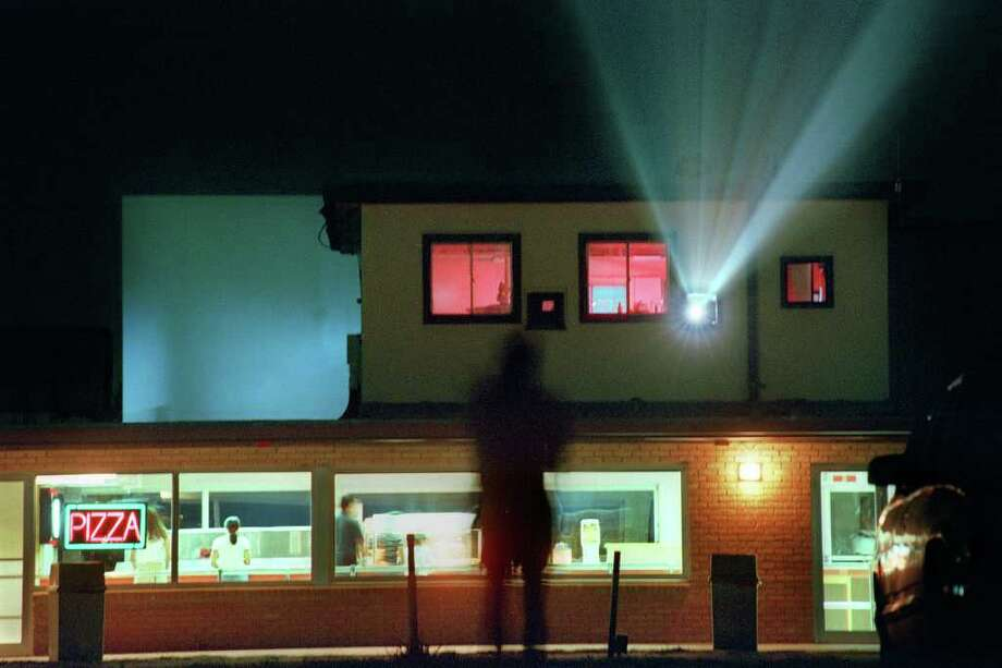 A movie watcher heads to the snack bar at the Mission 4 Outdoor Theatre on June 11, 1999. Photo: EDWARD A. ORNELAS