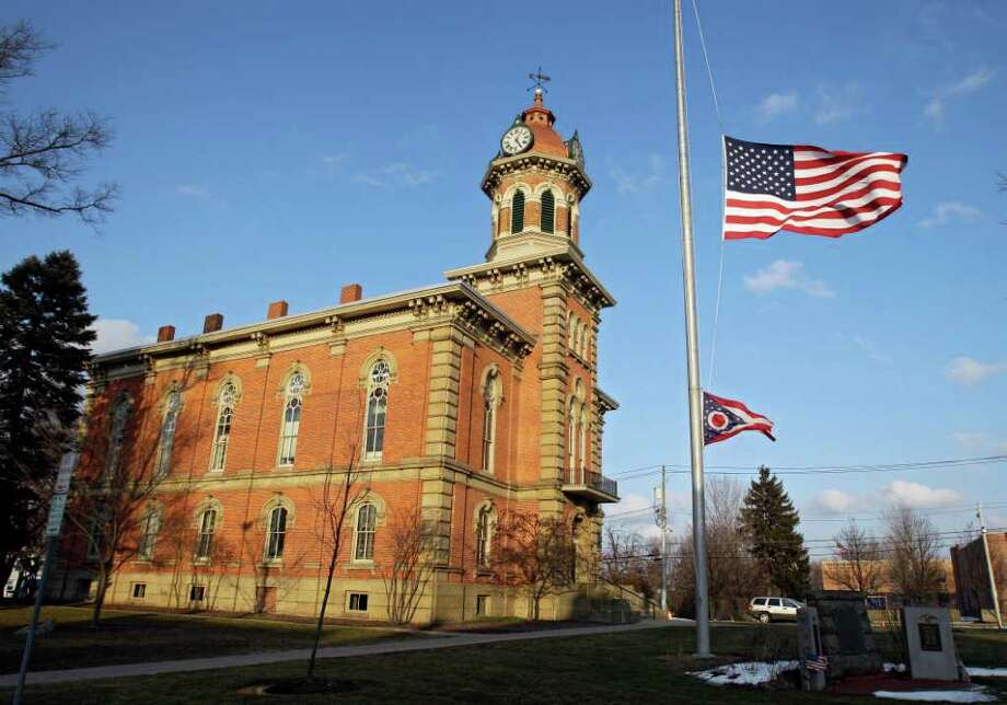 Flags fly at half staff in front of the town hall in Chardon, Ohio for the victims of an early morning school shooting Monday, Feb. 27, 2012. A gunman opened fire inside the high school's cafeteria at the start of the school day, killing one student and wounding four others.  (AP Photo/Mark Duncan) Photo: Mark Duncan, STF / 2011 The Associated Press