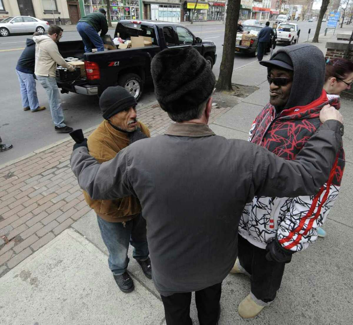 Soup kitchen regulars Antonio Otero, left, and Dumar Wilmer, right, are comforted by Rev. John Bradley at the site of the old Blessed Sacrament Community Kitchen at the corner of Central and Lake Avenue in Albany, N.Y., on Feb. 28, 2012. The new soup kitchen will be at the Sister Maureen Joyce Center. The community kitchen serves as many as 150 at one sitting and is operated by Blessed Sacrament Parish, and staffed by Catholic Charities, Temple Beth Emeth and others. Volunteers from the parish, the community, Catholic Charities and area colleges moved the kitchen with as many as nine trucks and other vehicles. ( Skip Dickstein / Times Union)