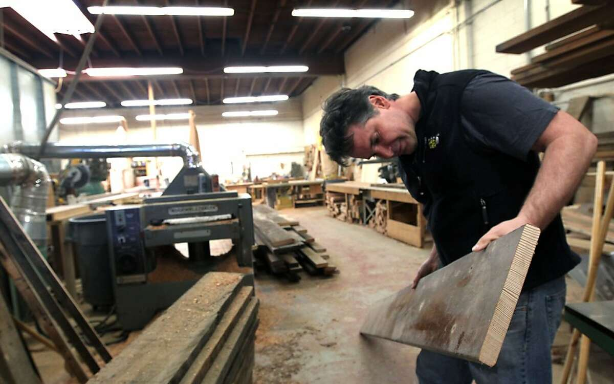 Eric Gellerman Co founder of The Wood Duck Furniture Co in Berkeley looks over old wood salvaged from San Francisco State bleachers that he plans to make his custom benches, tables and outdoor furniture from Friday February 17, 2012. Some of Gellerman most memorable pieces were made with recycled wood from Kezar Stadium's old wood benches.