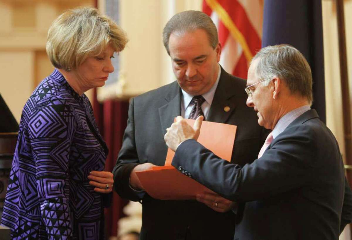 Lt. Gov. Bill Bolling, center looks over amendments to the ultrasound bill proposed by State Sen. Janet Howell, D-Fairfax, left, along with Senate Republican leader, Sen. Tomas Norment, R- James City, right, during debate on a bill requiring an ultrasound before an abortion on the floor of the Senate at the Capitol in Richmond, Va., Tuesday, Feb. 28, 2012. The Senate passed an amended bill. (AP Photo/Steve Helber)