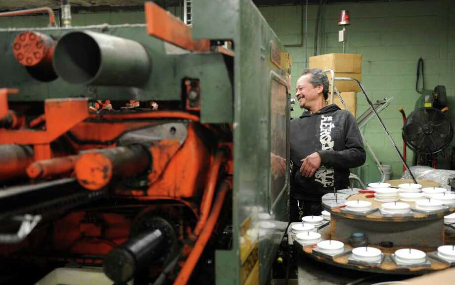 Eddie Ortiz operates an injection-molding machine making clothesline pulleys Tuesday, Feb. 28, 2012 at Penn Plastics, a full-service, family owned custom injection molder and manufacturer in Bridgeport, Conn. Photo: Autumn Driscoll / Connecticut Post
