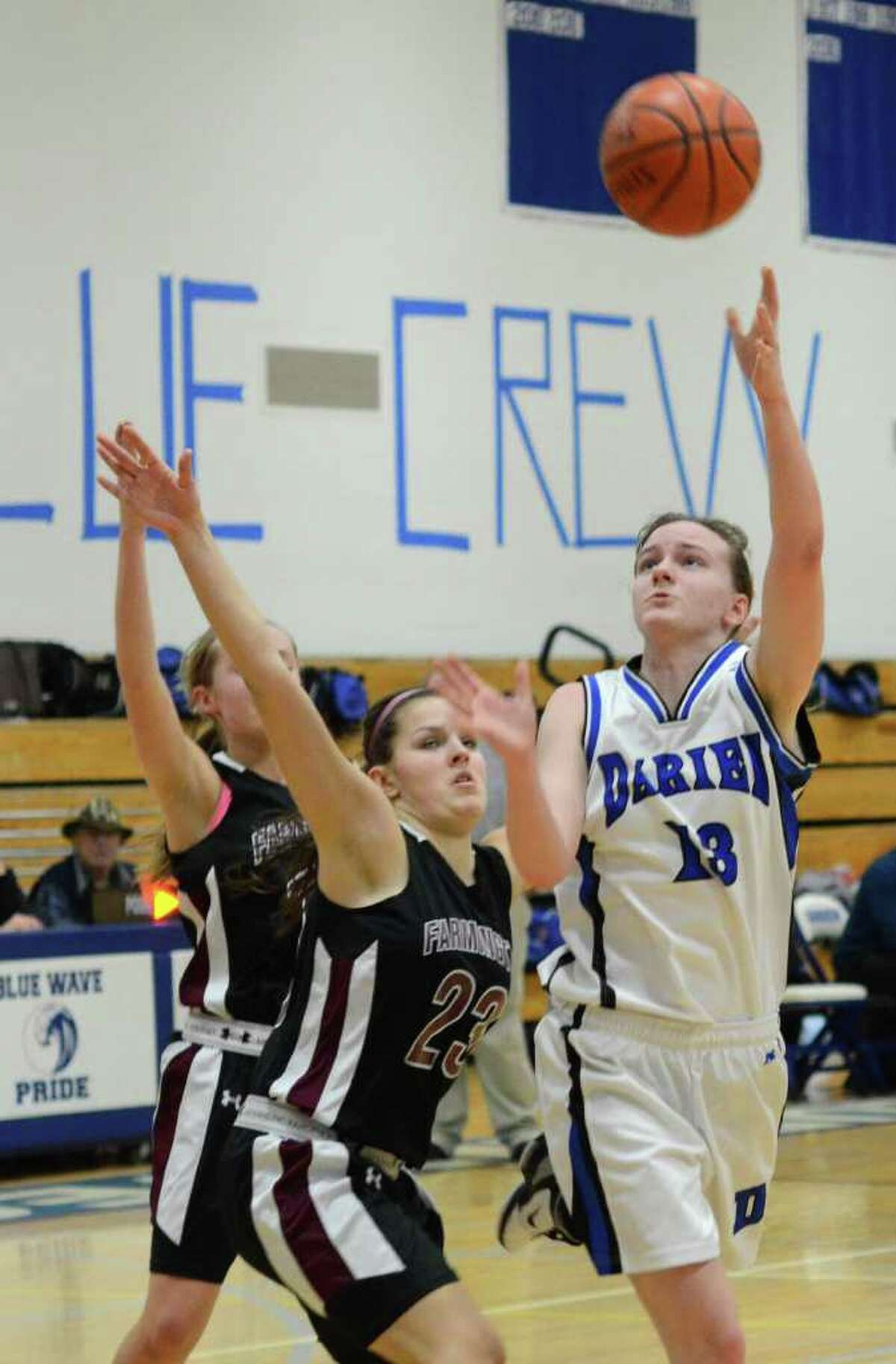 Darien's Kate Bushell (13) goes up for a shot against Farmington's Ugne Vaiciulyte (23) during the girls basketball game at Darien High School on Tuesday, Feb. 28, 2012.