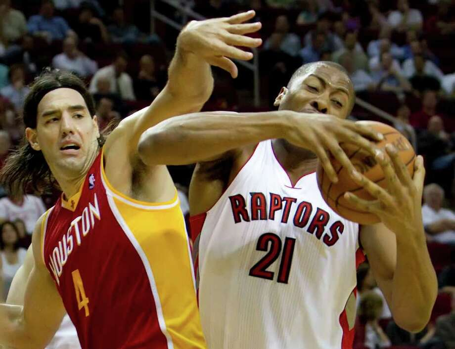 Jamaal Magloire (21) of the Toronto Raptors pulls down a rebound against Luis Scola (4) of the Houston Rockets on Tuesday, February 28, 2012, in Houston, Texas. (George Bridges/MCT) Photo: George Bridges, McClatchy-Tribune News Service / MCT