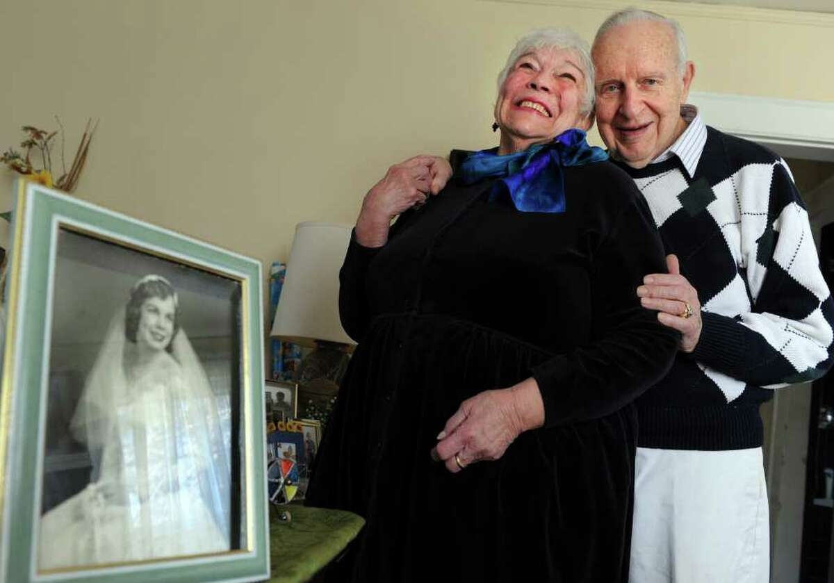 Jeanne and Wayne Harrison stand near a photo from their 1952 wedding Tuesday, Feb. 28, 2012 at their home in Fairfield. The couple has been married 60 years, or 15, depending on how you look at it. Their anniversary is Leap Day.