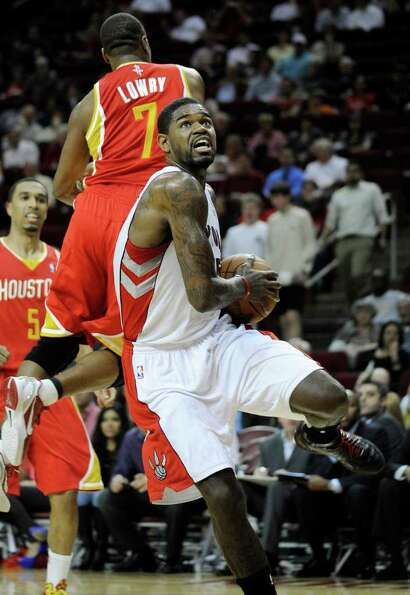 Toronto Raptors' Amir Johnson, front, heads to the basket after getting past Houston Rockets' Kyle L