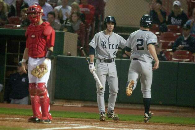 Rice third baseman Shane Hoelscher (2) is congratulated by teammate Jeremy Rathjen (4) as University of Houston catcher John Cannon (37) looks on after scoring on a RBI double by first baseman Ryan Lewis (16) during the fifth inning of a NCAA college baseball game at Cougar Field on Tuesday February 28, 2012 in Houston, TX. Photo: J. Patric Schneider, For The Chronicle / Houston Chronicle