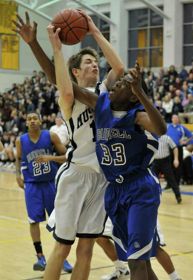 Immaculate's Brian Hatcher gets tangled up with Bunnell's Isaac Vann during their SWC semi-final game at Newtown High School on Tuesday, Feb. 28, 2012. Immaculate won 60-51. Photo: Jason Rearick / The News-Times
