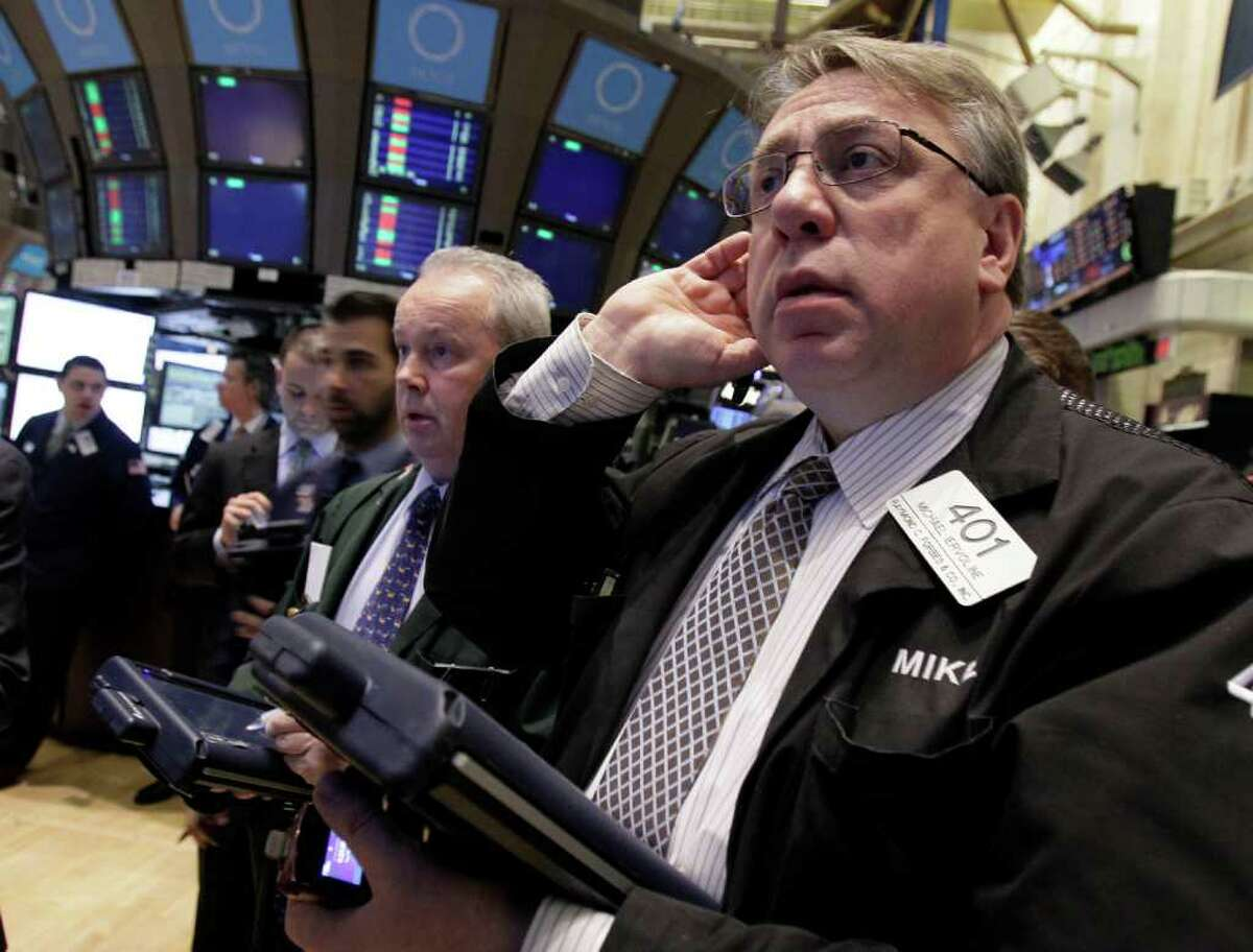 Trader Michael Iervoline, right, works on the floor of the New York Stock Exchange Tuesday, Feb. 28, 2012. Stocks are opening mixed after weak reports on factory orders and home prices. (AP Photo/Richard Drew)