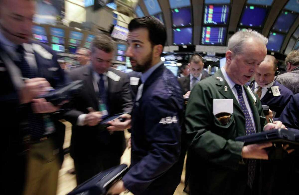 Trader Joseph Dente, center, moves through a crowd on the floor of the New York Stock Exchange Tuesday, Feb. 28, 2012. Stocks are opening mixed after weak reports on factory orders and home prices. (AP Photo/Richard Drew)