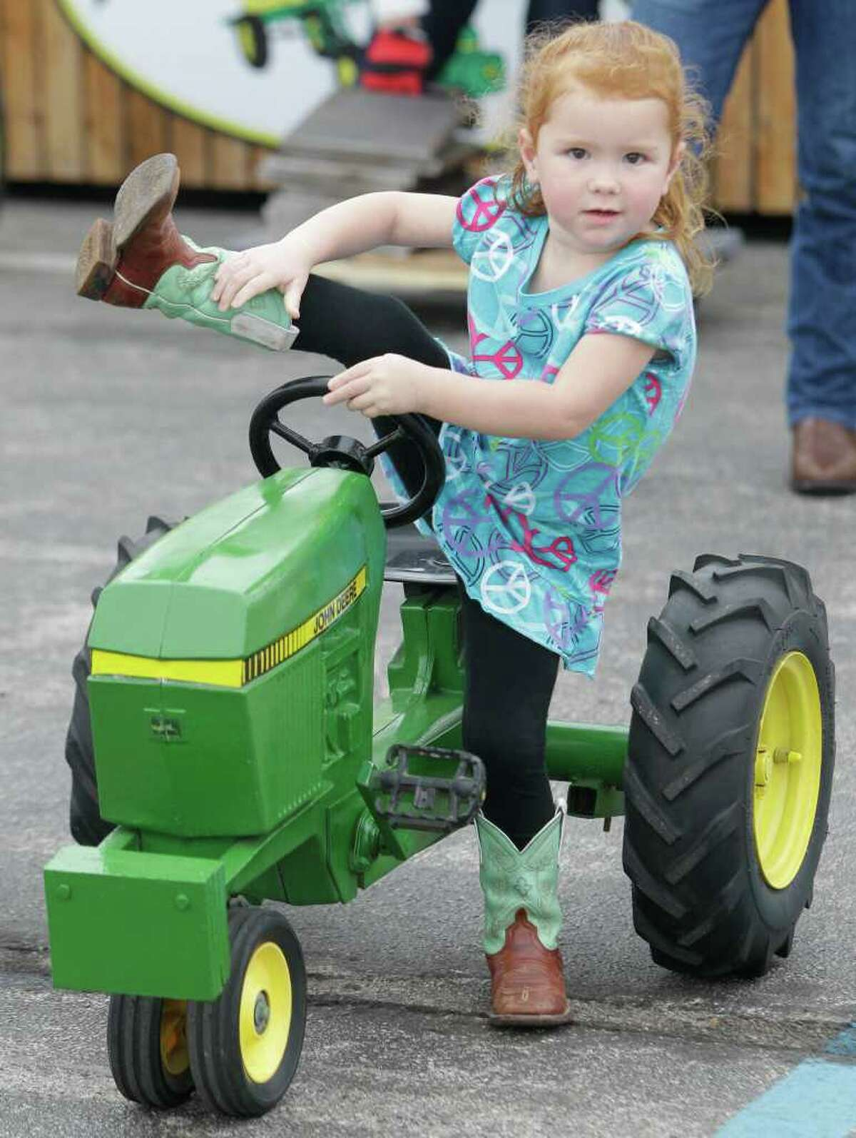 Mica Collins, 3, of Washington, Texas, tries to get a leg up at the Kids' Pedal Tractor Pull at the rodeo, but she was too young to compete.