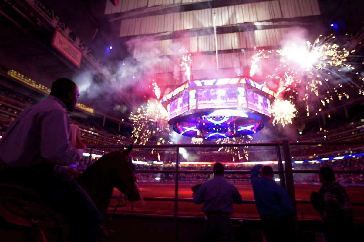Cowboys, and a steed, take in the fireworks during the national anthem on opening day at RodeoHouston Tuesday.