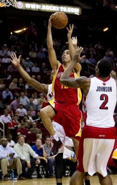 Kevin Martin (12) of the Houston Rockets goes for a shot between DeMar DeRozan (10) and James Johnso