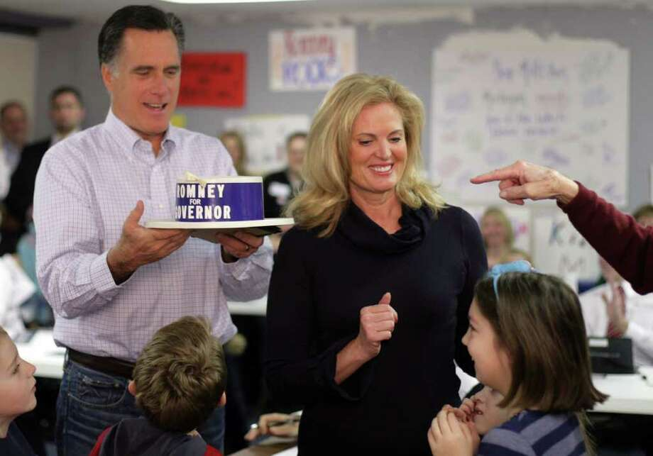 Republican presidential candidate Mitt Romney and his wife Ann, center, look over a hat from his dad's campaign for governor, Tuesday, February 28, 2012, at his campaign headquarters in Livonia, Michigan. Photo: ANDRE J. JACKSON, McClatchy-Tribune News Service / Detroit Free Press