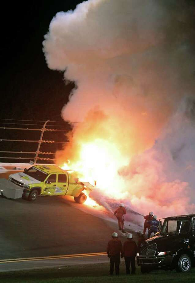 Emergency workers try to put out a fire on a jet dryer during the NASCAR Daytona 500 auto race at Daytona International Speedway in Daytona Beach, Fla., Monday, Feb. 27, 2012. (AP Photo/Bill Friel) Photo: Bill Friel