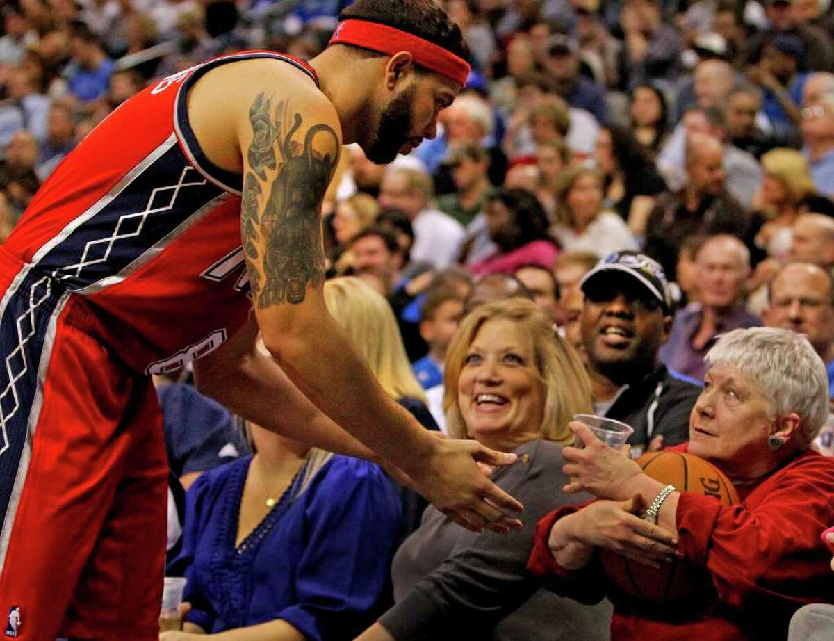Nets guard Deron Williams has trouble getting the ball back from courtside Mavs fan Sandi Gaylord.