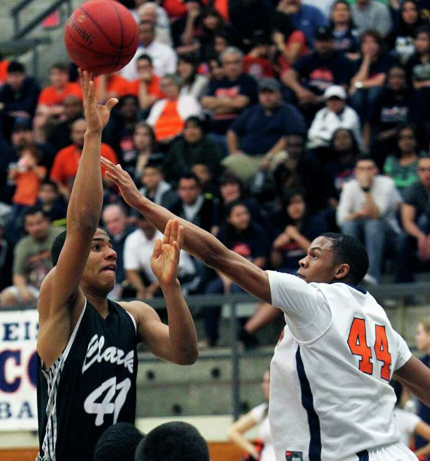 Clark post Shawn Gulley (left) gets off a shot despite the defensive efforts of Eric Robinson of Brandeis during the Class 5A third-round playoff game at Taylor Field House. The Cougars won 45-39. Photo: TOM REEL, San Antonio Express-News / San Antonio Express-News