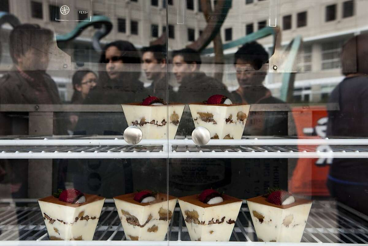 People waiting in line at the Koja Kitchen food truck on 2nd and Folsom Streets are reflected from the dessert case on Tuesday, February 28, 2012 in San Francisco, Calif.