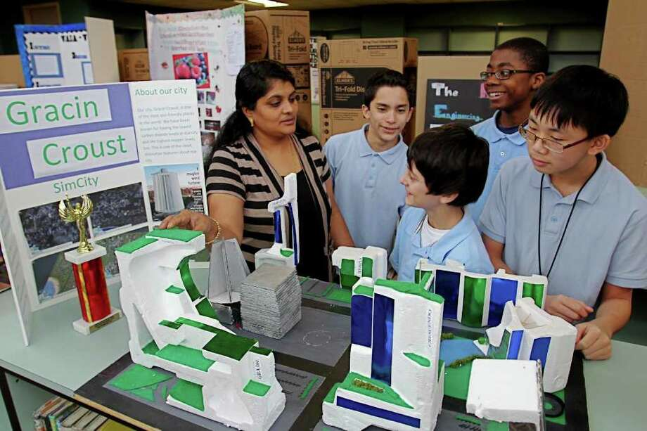 Preeti Joseph, an eighth-grade science teacher at Stafford Middle School, looks at her students' science project. Students, from left, are Cristian Ortiz, 14; Nikola Radojevic, 13; and Gerald Ucheghu, 14; and Richard Tran, 13. Photo: Suzanne Rehak