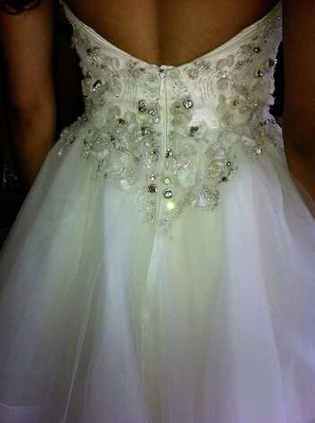 Embellishments on the bodice of this gown by Jim Helm, $3,900 at Bridal Salon of San Antonio, add drama for the bride walking down the aisle.
