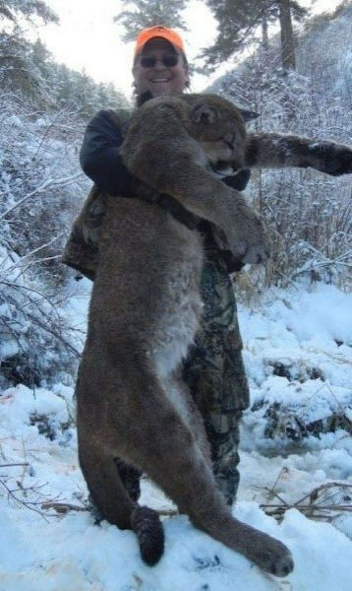 Former California Fish and Game Commission President Daniel Richards was photographed showing him grinning as he holds up the body of a mountain lion he shot, killed and ate in Idaho.