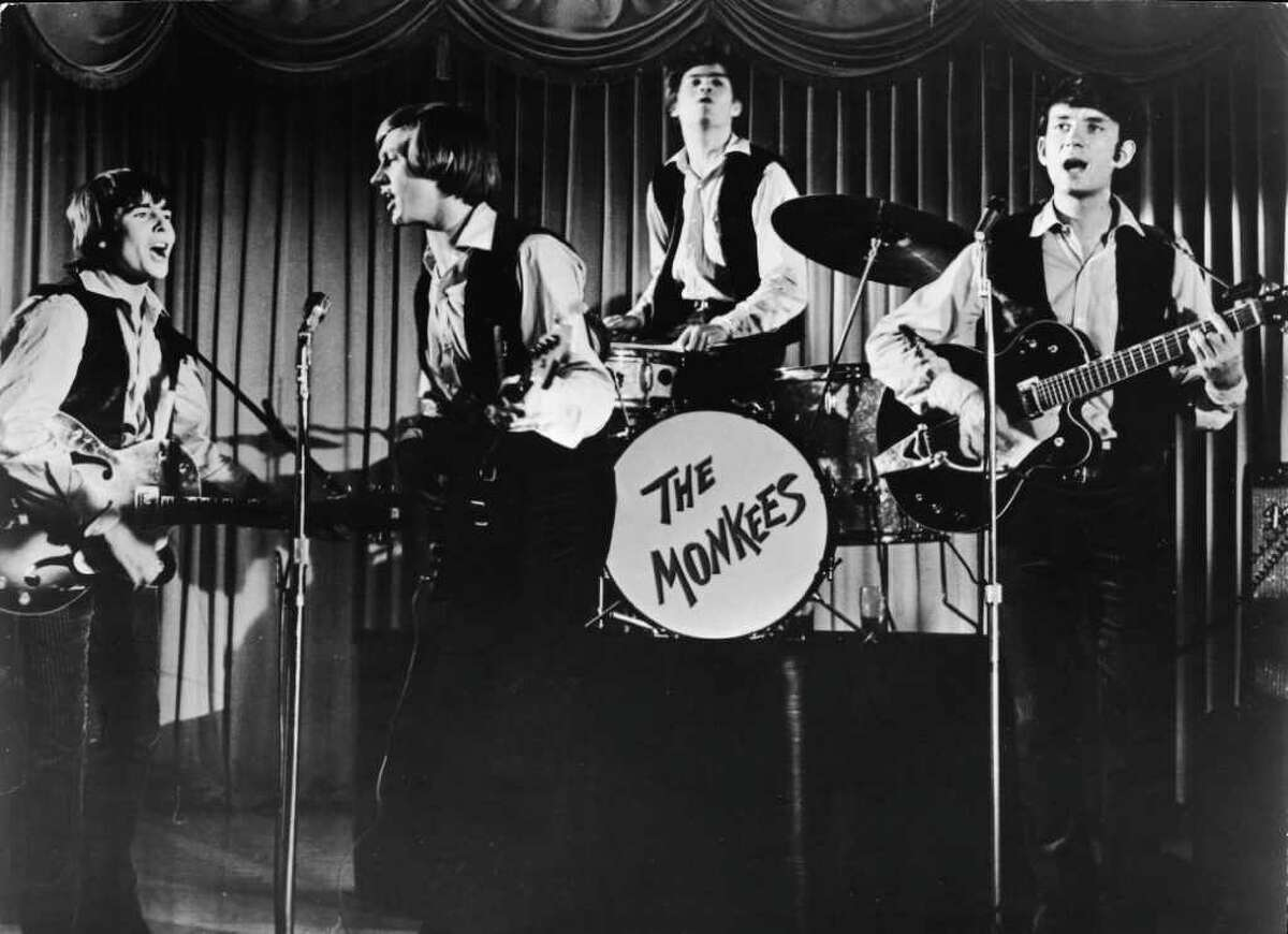 Television still shows the popular music and television group the Monkees as they perform onstage in an episode of their self-titled tv show, late 1960s. From left, Davy Jones, Peter Tork, Mickey Dolenz (on drums), and Michael Nesmith.