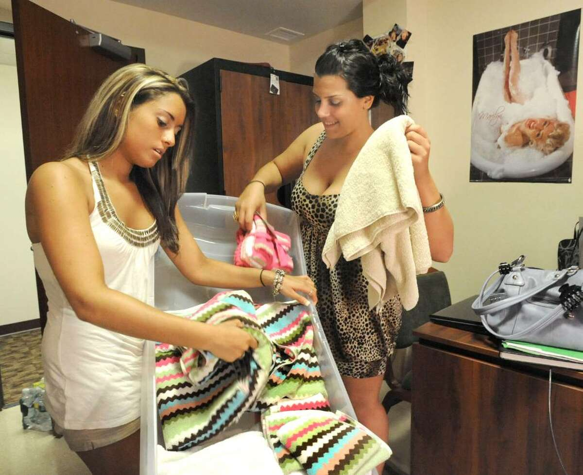 New students Jessica DeLillo of Seymore, left and Ashley Kopsick of Franklin Square, Long Island, unpack as they move in to Fairfield Hall dorm on the WCSU doewntown campus on Aug. 28, 2009.