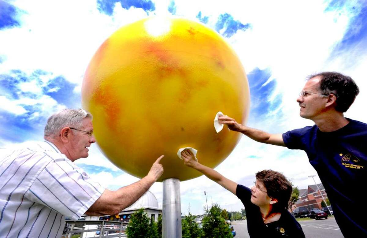 Parker Moreland, left, Cecilia Page and Randy Fender wipe off the sun, which is the center of the scale model of the solar system at the John J. McCarthy Observatory at New Milford High School on Aug.24, 2009.