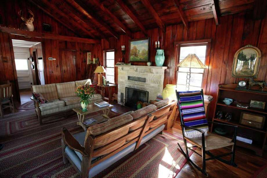 Tibbits and a helper scrubbed and shellacked the pine on the walls and ceiling in the living room; they had been blackened by years of burning cedar in the fireplace. The fireplace was taken apart, repaired and put back in place exactly as it had been built in the 1940s. Photo: DANNY WARNER