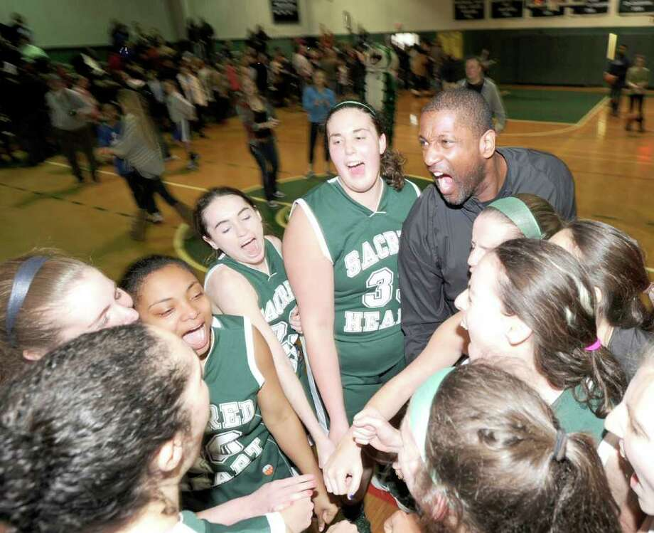 Coach Sean Green, right, and his Convent of the Sacred Heart basketball team react after winning the FAA girls high school basketball championship over School of the Holy Child on Saturday. Convent defeated Holy Child 63-45 to win the championship. Photo: Bob Luckey / Greenwich Time